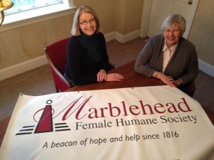 Marblehead Female Humane Society 200th Anniversary Co-Chairs Barbara Miller and Judith O'Leary present the organization's new logo. The design is based on Bob Baker's original logo and tagline concepts and produced by graphic designer Peter Schalck.